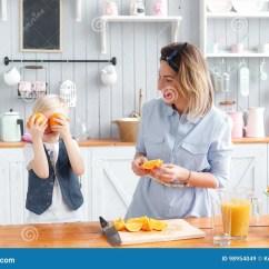 Kids Wood Kitchen Stainless Steel Single Bowl Sink 孩子闭上橙色他的眼睛在唬弄附近在厨房里吃早餐的儿子和年轻母亲库存图片 在厨房吃早餐妈妈的儿子和年轻母亲切果子给她的儿子在一个木切板的切的桔子早餐健康鲜美