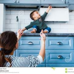 Kid Kitchens Kitchen Floor Cupboards 小孩孩子在厨房 儿童安全在家概念里库存图片 图片包括有求知欲 国内 妈妈保护孩子免受危险在厨房里