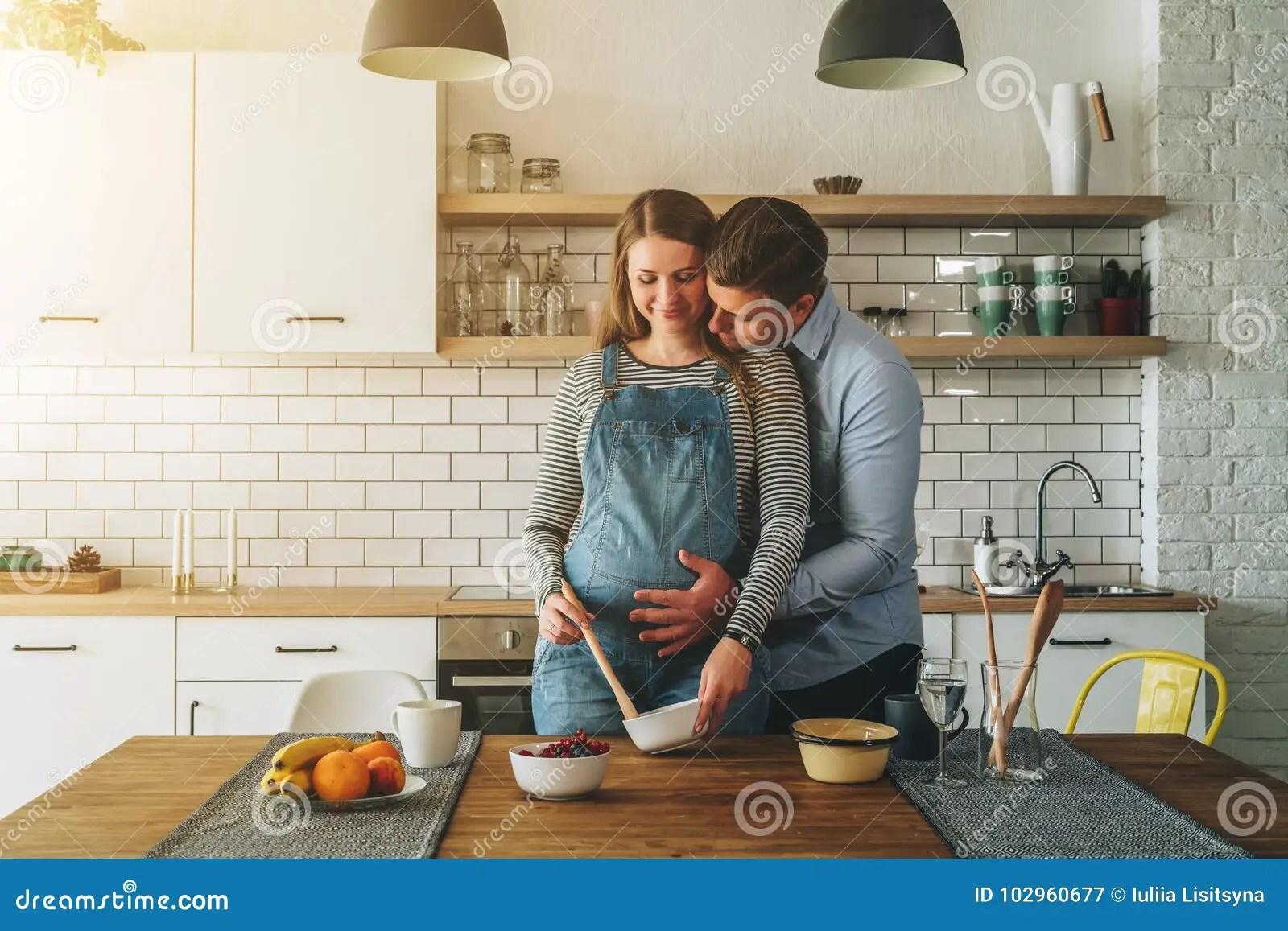 kitchen prep table solid wood cabinets 年轻人已婚夫妇在厨房里拥抱常设近的桌他的拥抱丈夫怀孕的妻子库存图片 年轻人已婚夫妇在厨房里拥抱常设近的桌丈夫拥抱他怀孕的妻子 把他的手放在她的大腹部上 妇女准备早餐生活方式 在爱的夫妇 愉快的人民