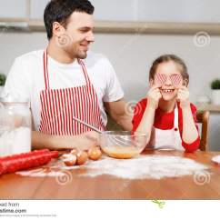 Kids Wood Kitchen Cheap Trash Can 快乐的深色的男性佩带围裙神色在用心脏盖眼睛的愉快的孩子 坐在木厨房用 坐在木厨房用桌 在碗的mixe鸡蛋上与一起扫 有好时间家庭和童年概念