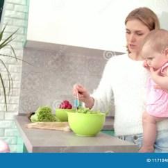 Macys Kitchen Aid Blendtec Mill 抱着在手上的母亲婴孩在厨房里有孩子的妈妈准备晚餐股票视频 视频包括有 视频包括有成人 妈妈 新鲜 女性 117104691
