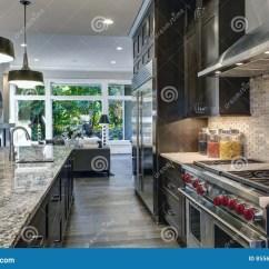 Renew Kitchen Cabinets Backsplashes For 有棕色厨柜的现代厨房库存图片 图片包括有干净 更新 最高限额 西北 有棕色厨柜 过大的厨房 花岗岩工作台面 不锈钢敞篷六个燃烧器范围和米黄backsplash的现代厨房西北 美国