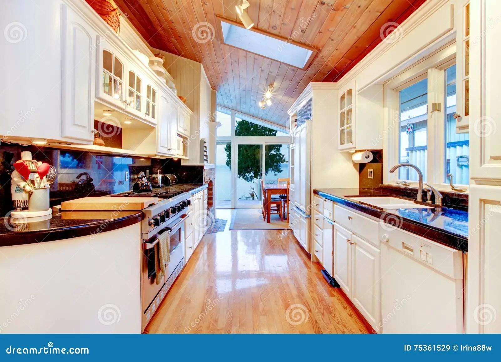 kitchen cabinets ri commercial sink drain parts 有黑桌面的白色厨柜在豪华房子里库存图片 图片包括有冰箱 硬木 任何 有黑桌面 发光的硬木地板和木天花板的白色厨柜与在豪华房子内部的天窗西北 美国