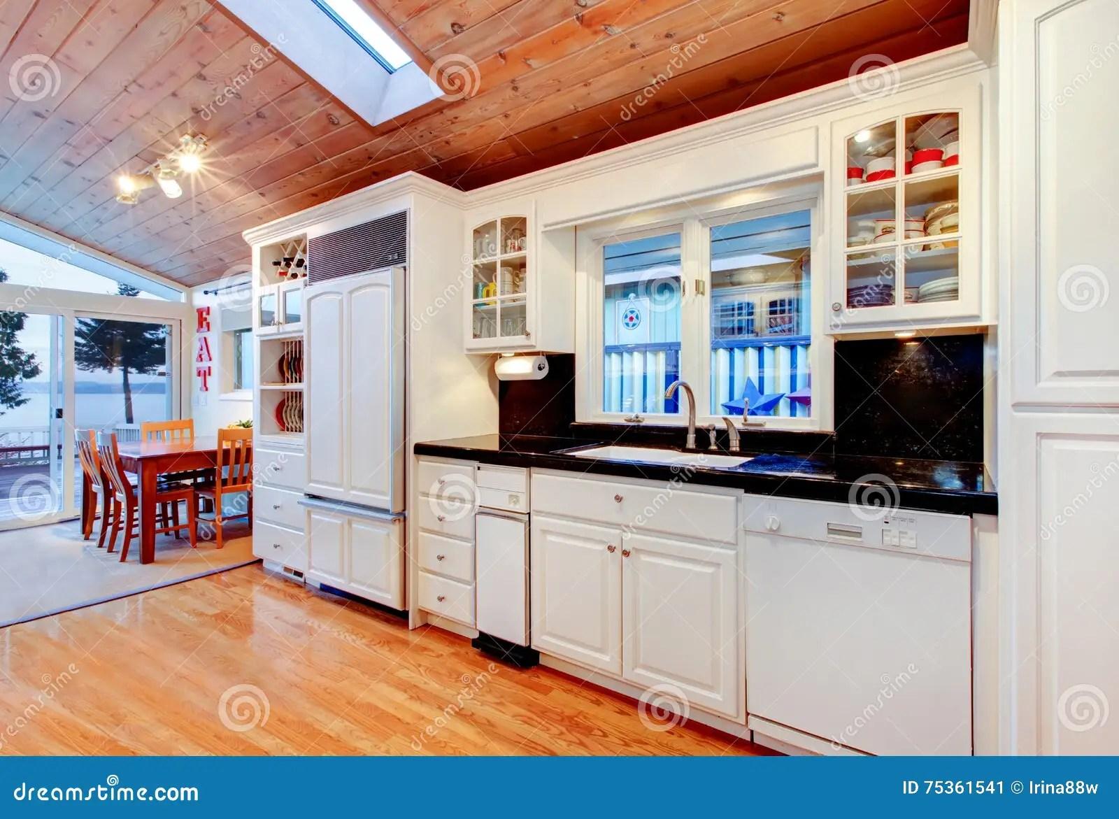 kitchen cabinets ri stick on backsplash tiles for 有黑桌面的白色厨柜在豪华房子里库存图片 图片包括有水槽 厨房 拱道 有黑桌面 发光的硬木地板和木天花板的白色厨柜与在豪华房子内部的天窗西北 美国