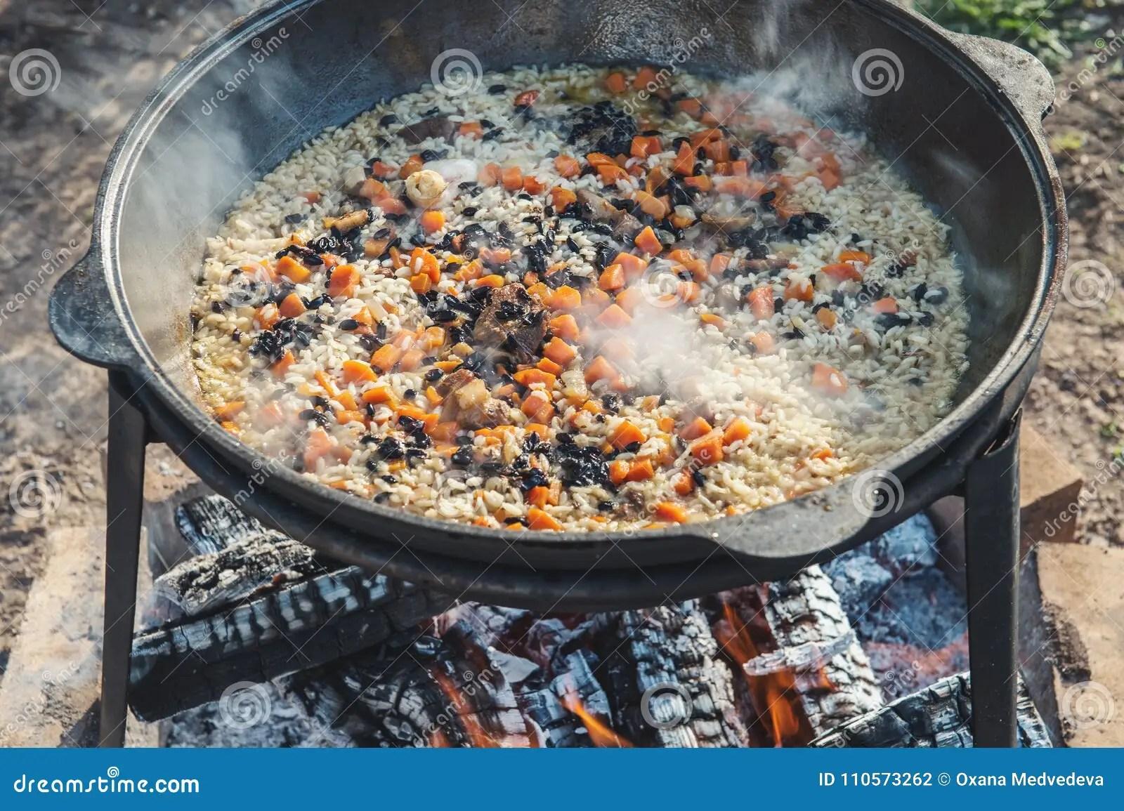 outdoor kitchen frames garbage cans walmart 烹调在一口大大锅的肉饭有一强蒸的在开火户外在一个晴朗的夏日关闭库存 烹调在一口大大锅的肉饭有一强蒸的在开火户外在一个晴朗的夏日一个水平的框架