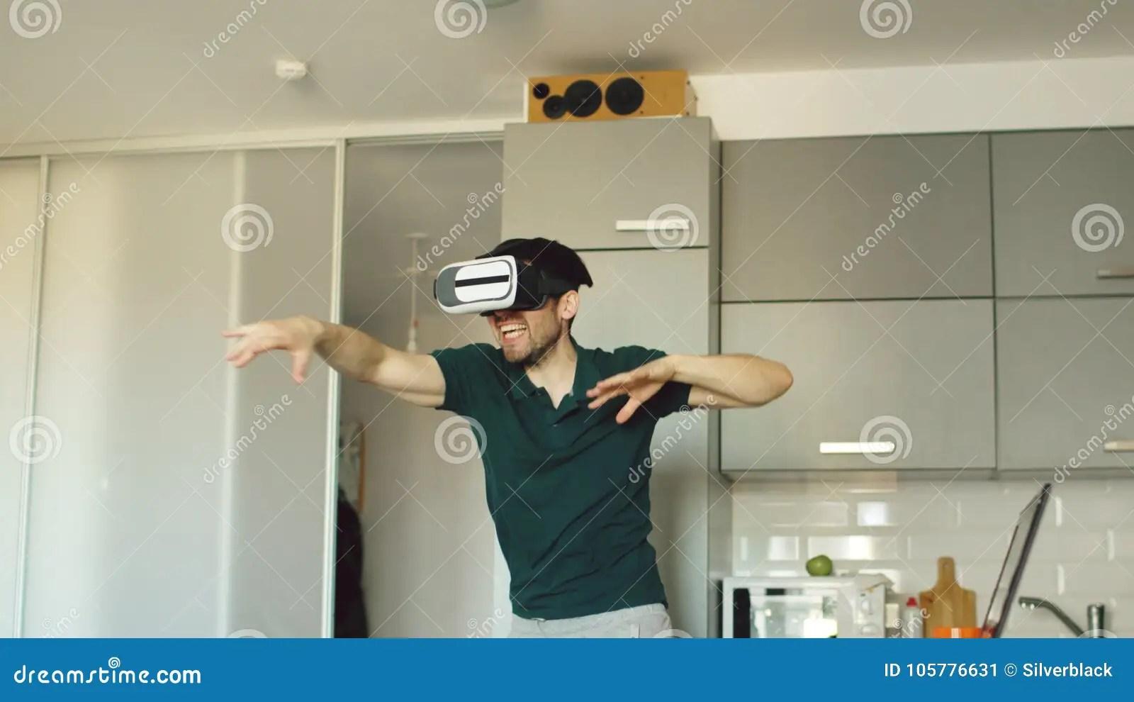 virtual kitchen single handle faucet with sprayer 虚拟现实360耳机跳舞的滑稽的年轻人在厨房早晨 当听到音乐时和获得乐趣 当听到音乐时和在家获得乐趣