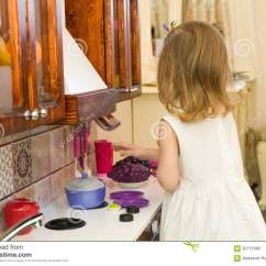 Kids Wood Kitchen Seating Ideas 活跃矮小的学龄前年龄孩子 有白肤金发的卷发的逗人喜爱的小孩女孩 显示 在厨房显示演奏厨房 由木头制成 戏剧