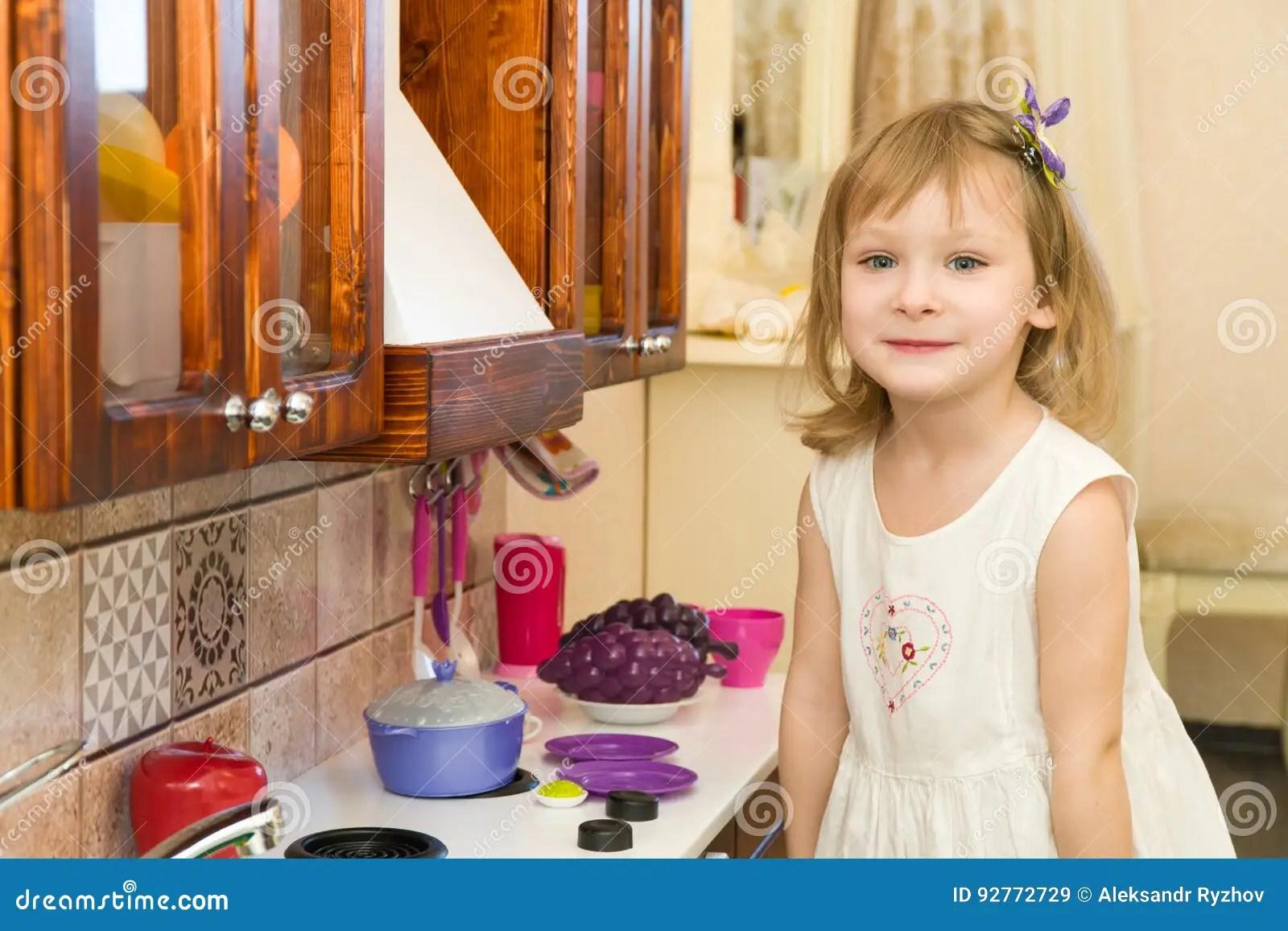 kids wooden kitchen tables and more 活跃矮小的学龄前年龄孩子 有白肤金发的卷发的逗人喜爱的小孩女孩 显示 在厨房显示演奏厨房 由木头制成 戏剧