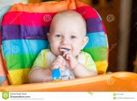 Adorable Baby Eating In High Chair Stock Photo - Image ...