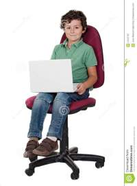 Adorable Little Boy Sitting On Big Chair With Lapt Stock