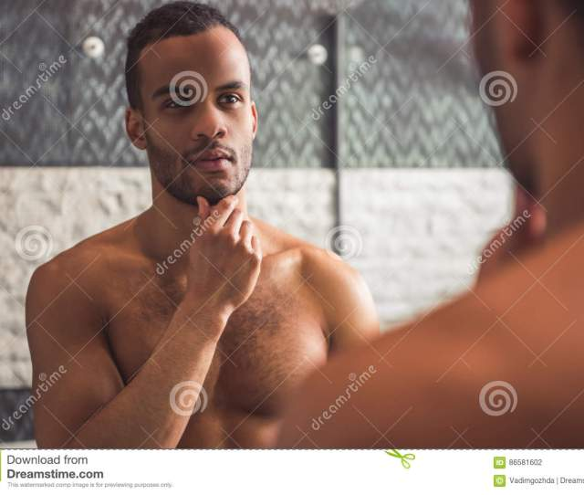 Handsome Naked Afro American Man Is Examining His Face While Looking Into The Mirror In Bathroom