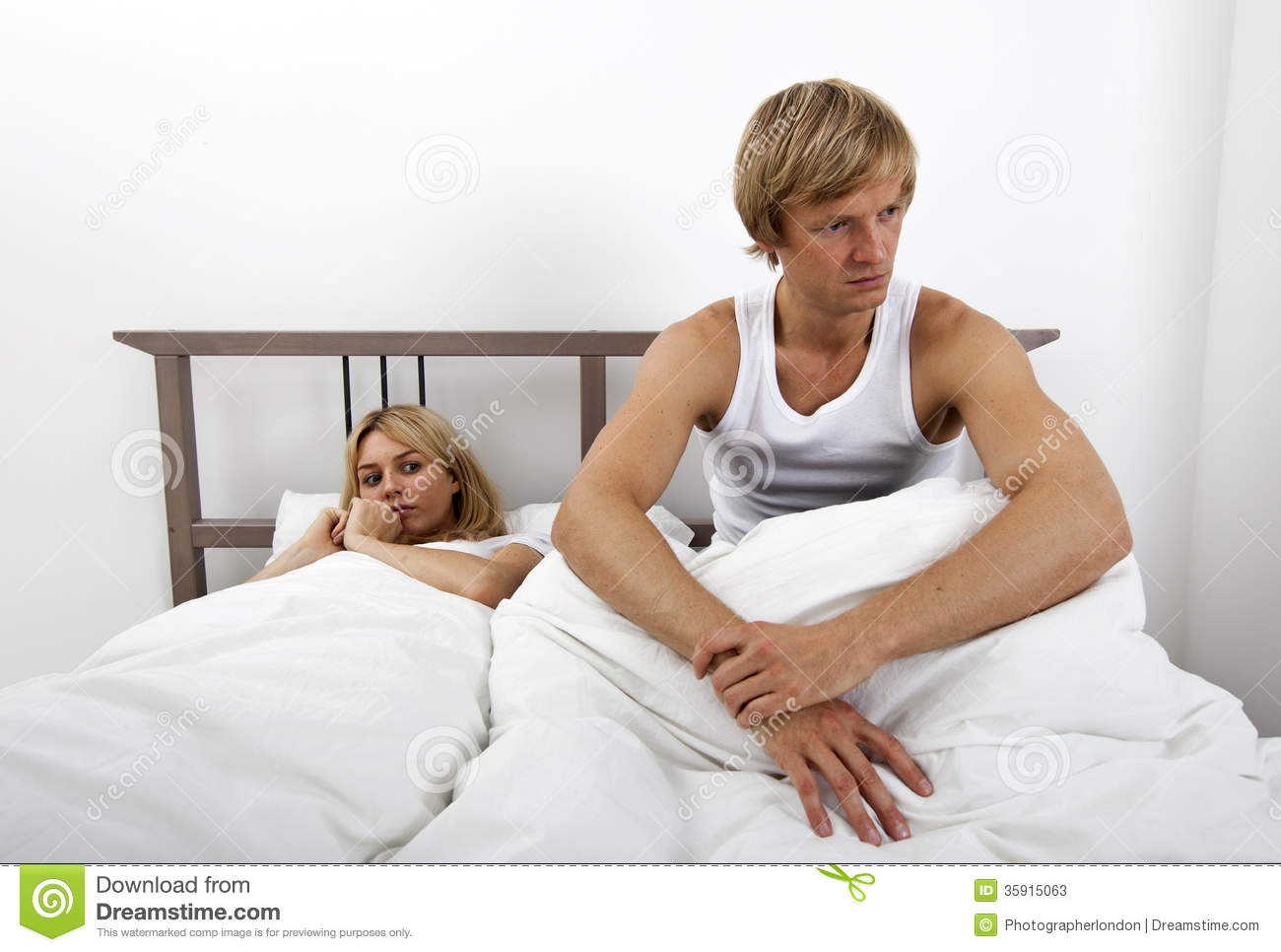 Angry Man Sitting On Bed With Woman In House Stock Image