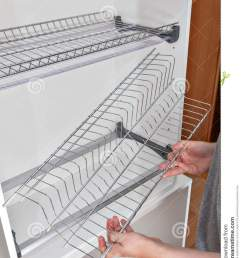 install wall mounted shelf under kitchen cabinet with inside dish rack with drip tray close up of a woman hands holds wire part  [ 1004 x 1300 Pixel ]