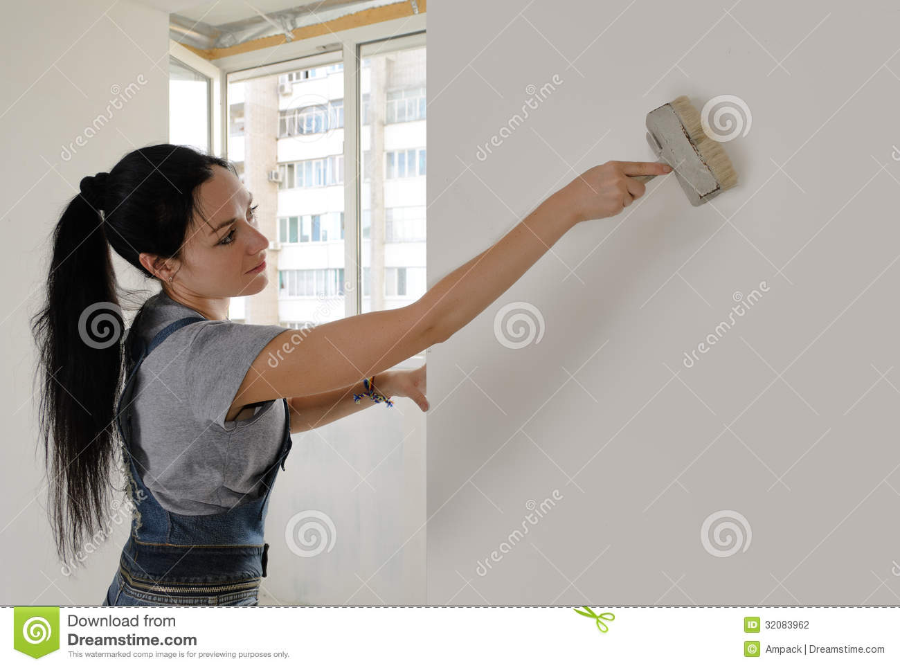 Attractive Woman Painting A House Wall Stock Photography