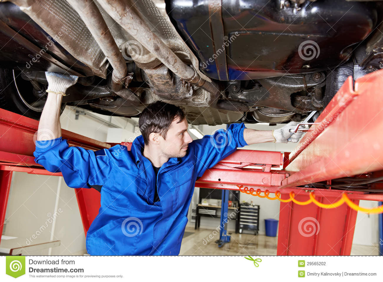 Auto Mechanic At Wheel Alignment Work With Spanner Stock