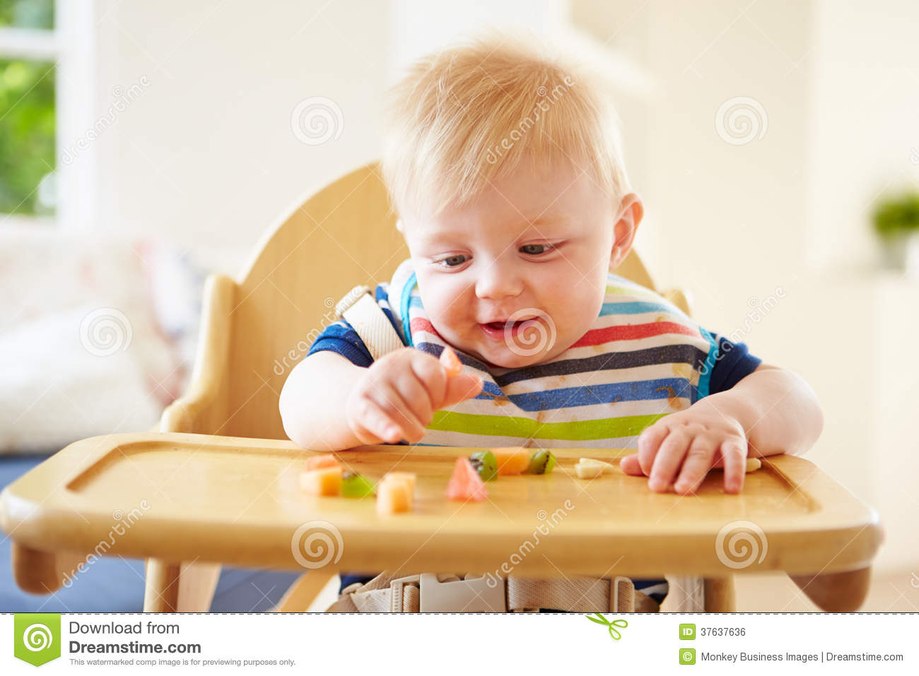 Baby Chair For Eating Baby Boy Eating Fruit In High Chair Royalty Free Stock