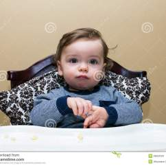High Chair For Boy Dining Accessories Baby Sits In Plays With Hands Stock Photo