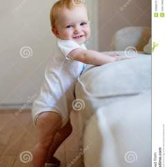 Toddler Boy Chair Umbra Oh Baby Standing Up Against A Couch Stock Photos - Image: 15066573