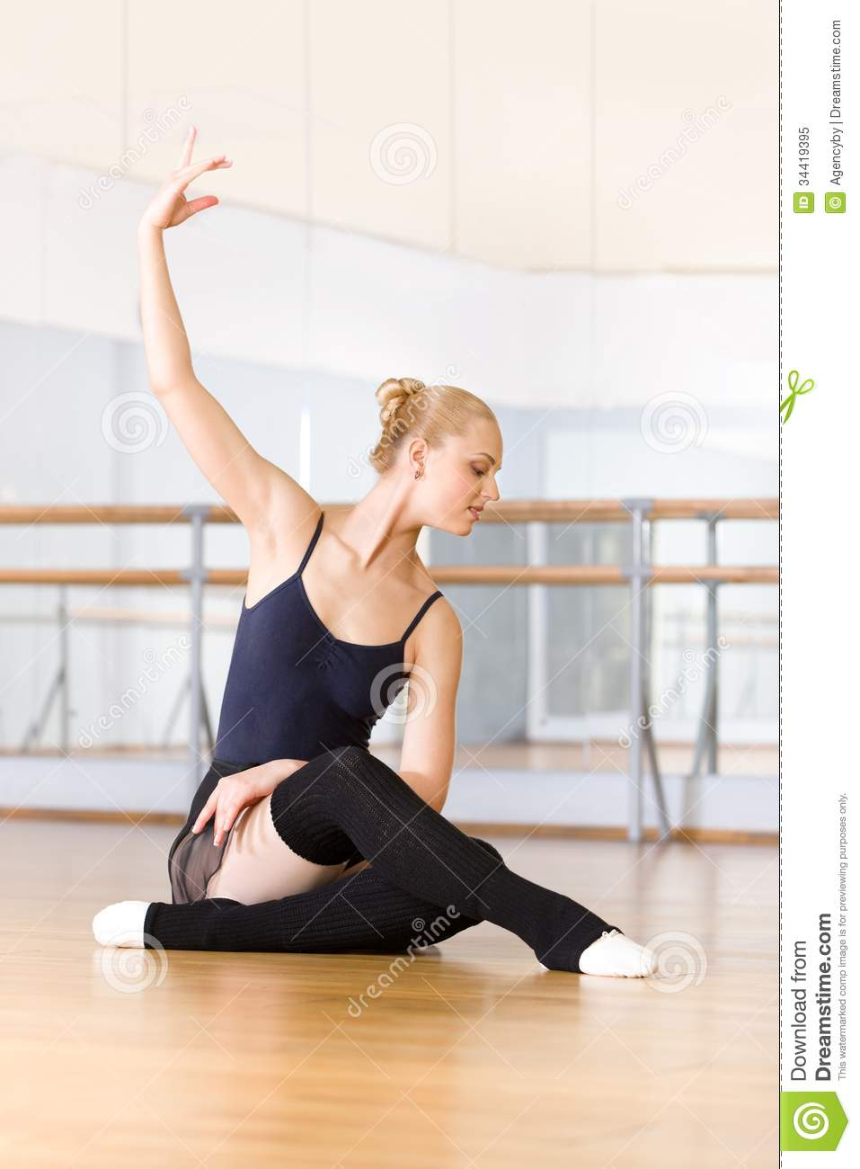 ballet dancer does exercises sitting floor works out wooden classroom barre mirrors 34419395