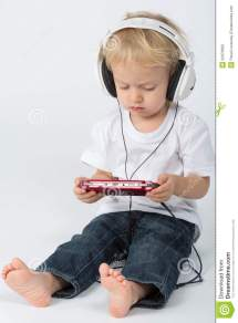 Barefoot Boy In Blue Jeans With Headphones Playing Stock