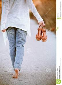 Girl Walking Barefoot Holding Shoes