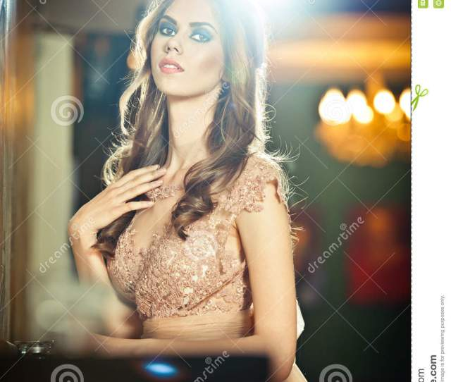 Beautiful Woman In Nude Lace Dress Posing In Vintage Scenery With Bright Lights