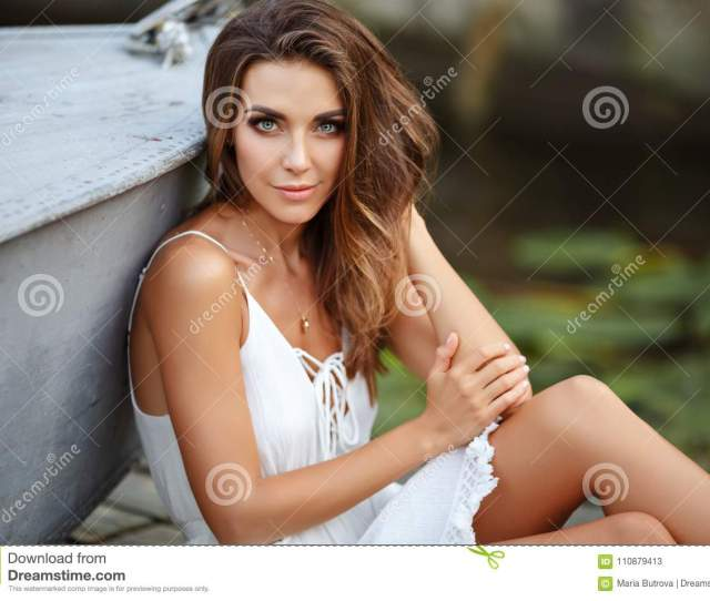 A Beautiful Tanned Girl In A White Dress Sits By The Boat And Is