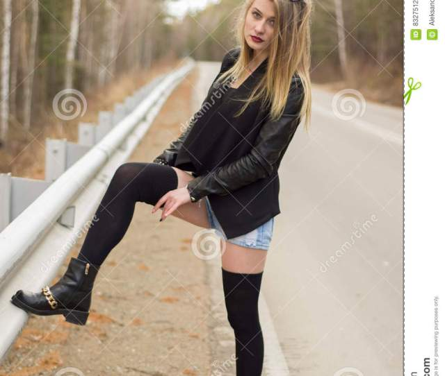 Beautiful Young Girl Corrects Stockings Leaning On The Guardrail