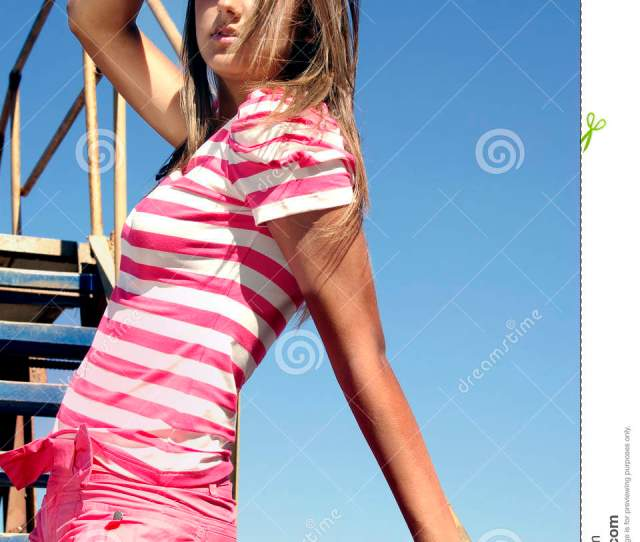 Young Beauty On The Ladder Over Sky Touches Hair