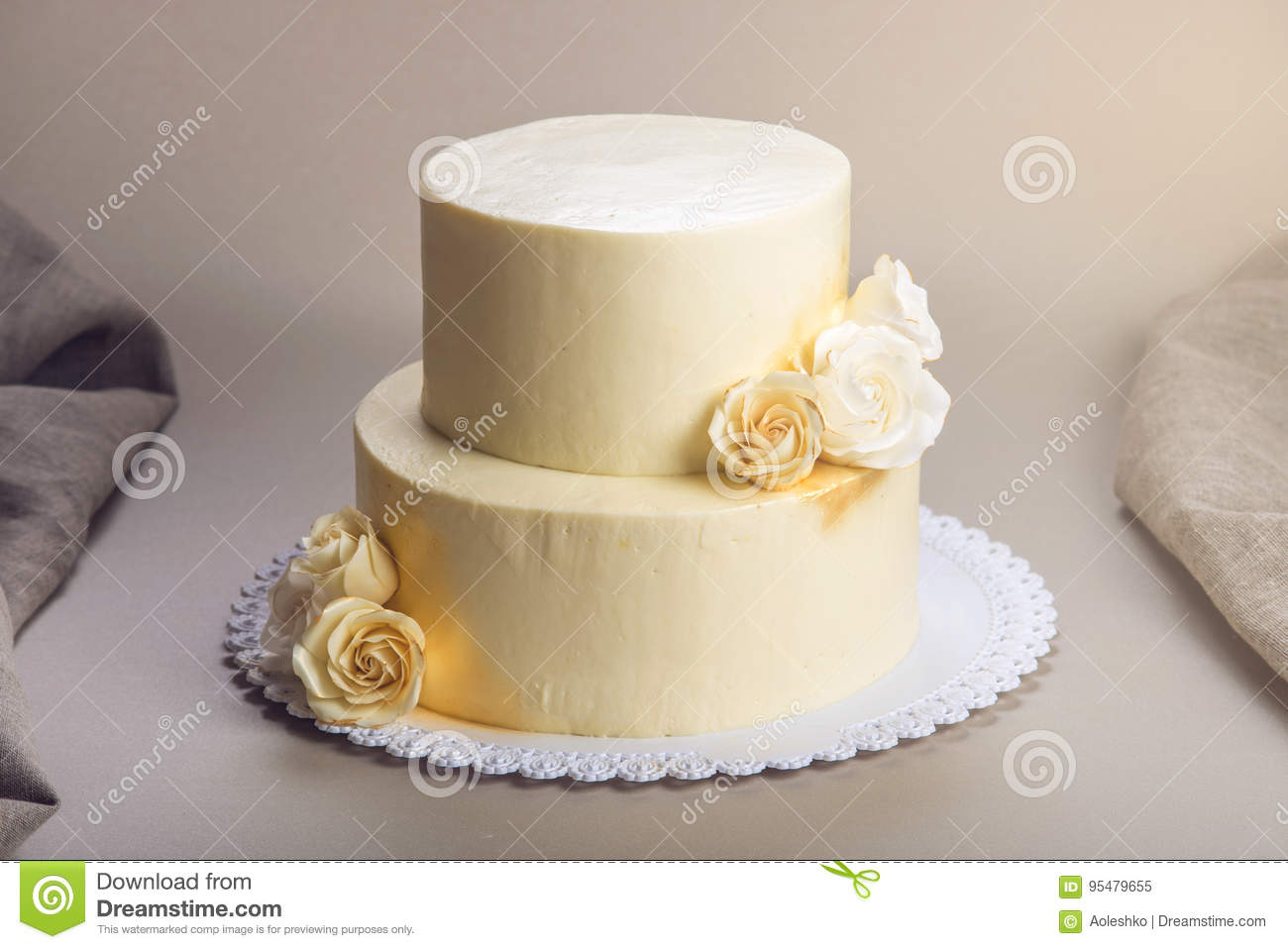 Beige 2 Tiered Wedding Cake Decorated With Mastic Roses Stands On