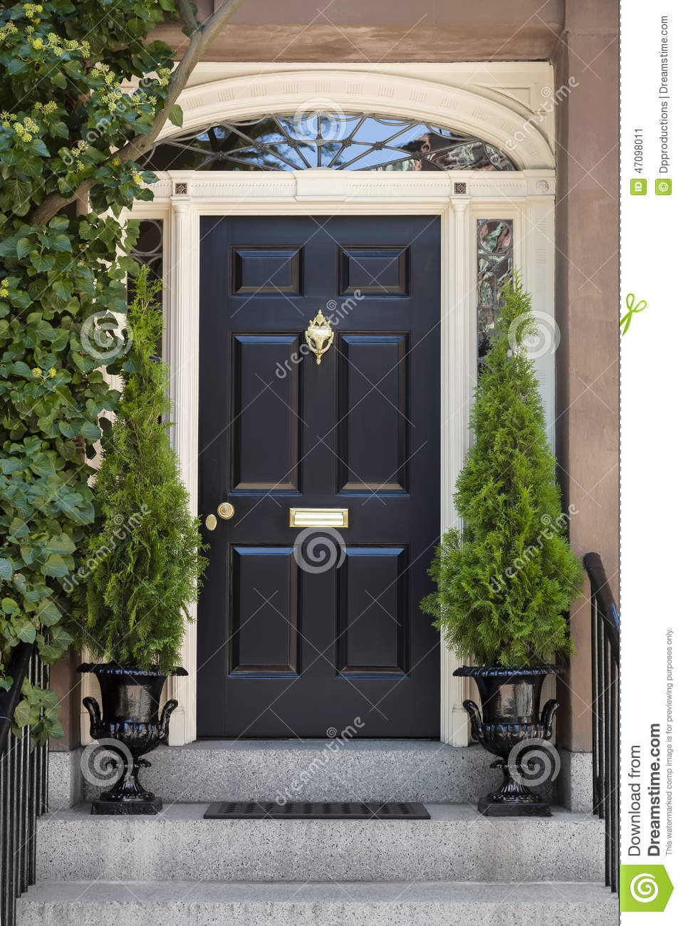 Black Front Door With White Door Frame And Greenery Stock