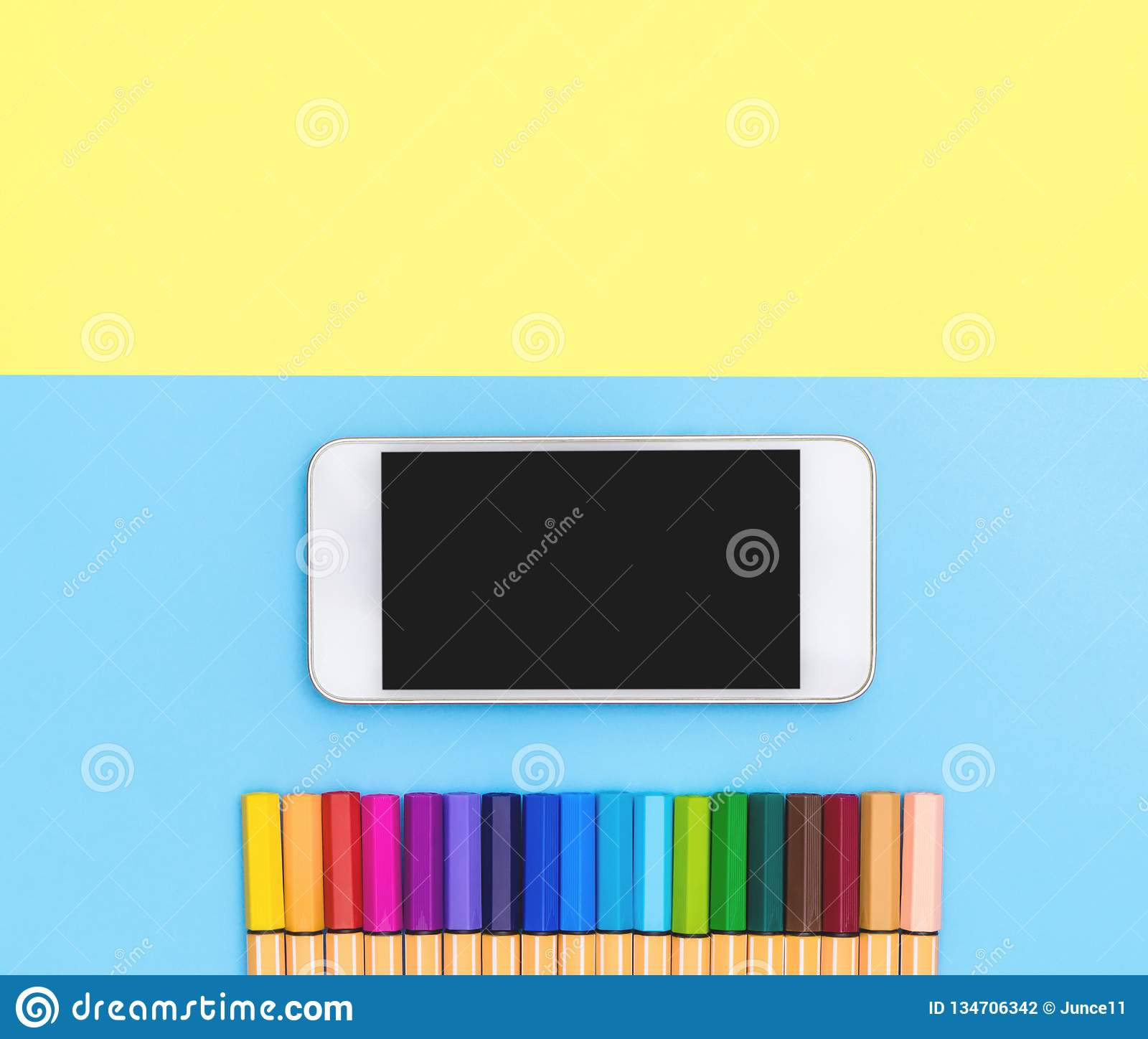 hight resolution of blank mobile phone and color marker pen line up on blue and yellow