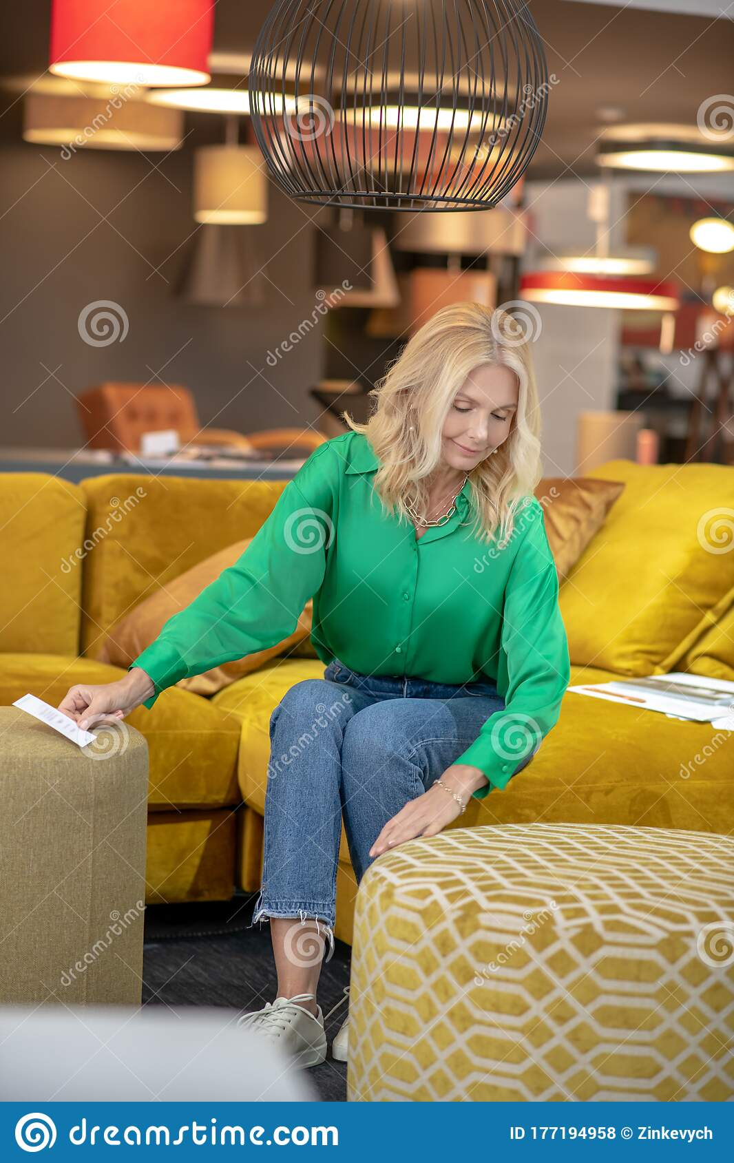 Blonde Woman In A Green Blouse And Jeans Sitting On A Yellow Sofa Stock Photo Image Of Blonde Involved 177194958