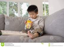 Boy With Coloring Book Sitting Sofa Stock