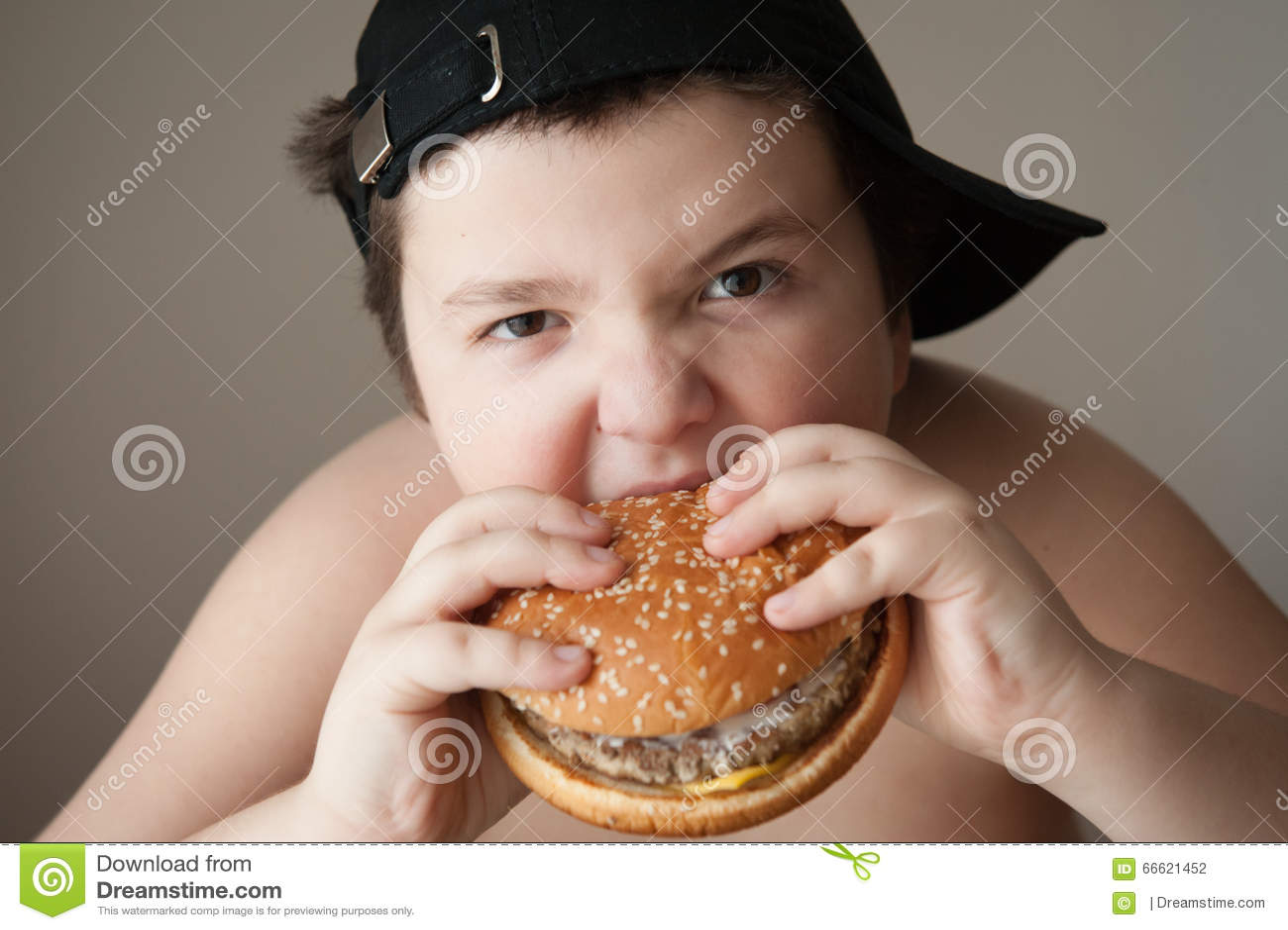 hight resolution of fat boy in cap eats a hamburger
