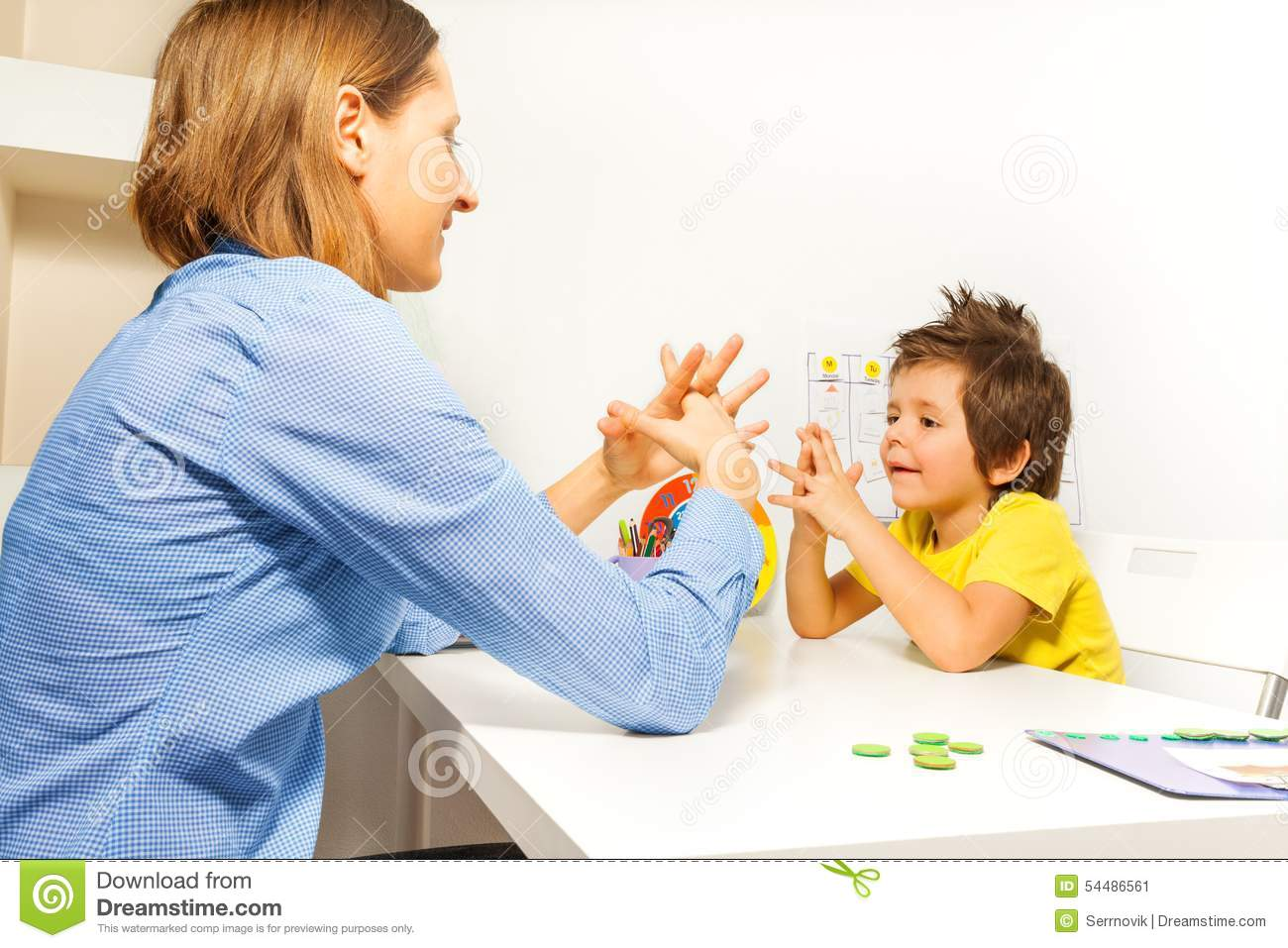 Boy Exercises Putting Fingers With Therapist Stock Photo