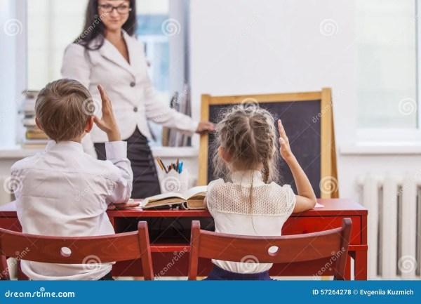 Boy And Girl Children With Teacher In School