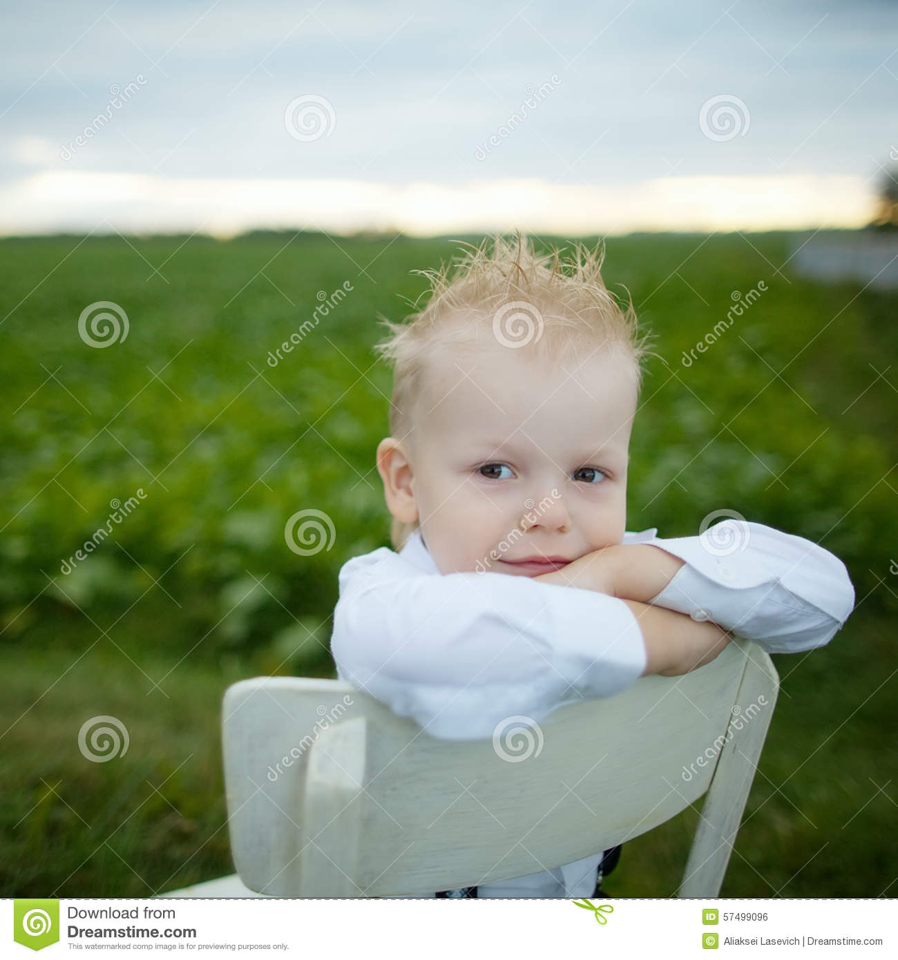 little boy chairs round chair and a half with ottoman sits on in the field stock photo image 57499096