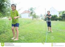 Boy Splashing Kid With Garden Hose Stock