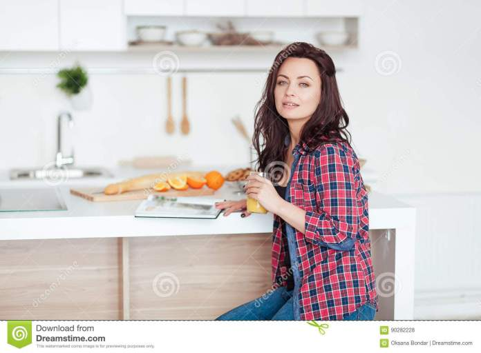 breakfast - smiling woman reading book in white kitchen, fresh