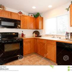 Black Kitchen Appliances Blue And Yellow Curtains Brown Cabinets With Stock Photo Image Of