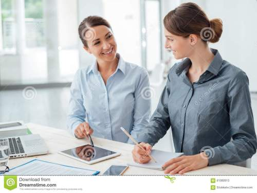 small resolution of business women working together on a tablet stock photo