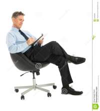 Businessman Writing In Note Pad While Sitting On Office ...