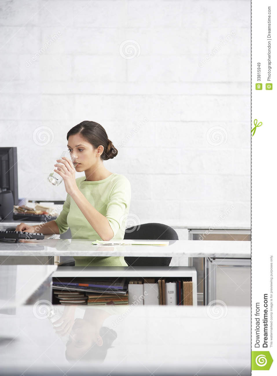 Businesswoman Drinking Water At Computer Desk Royalty Free