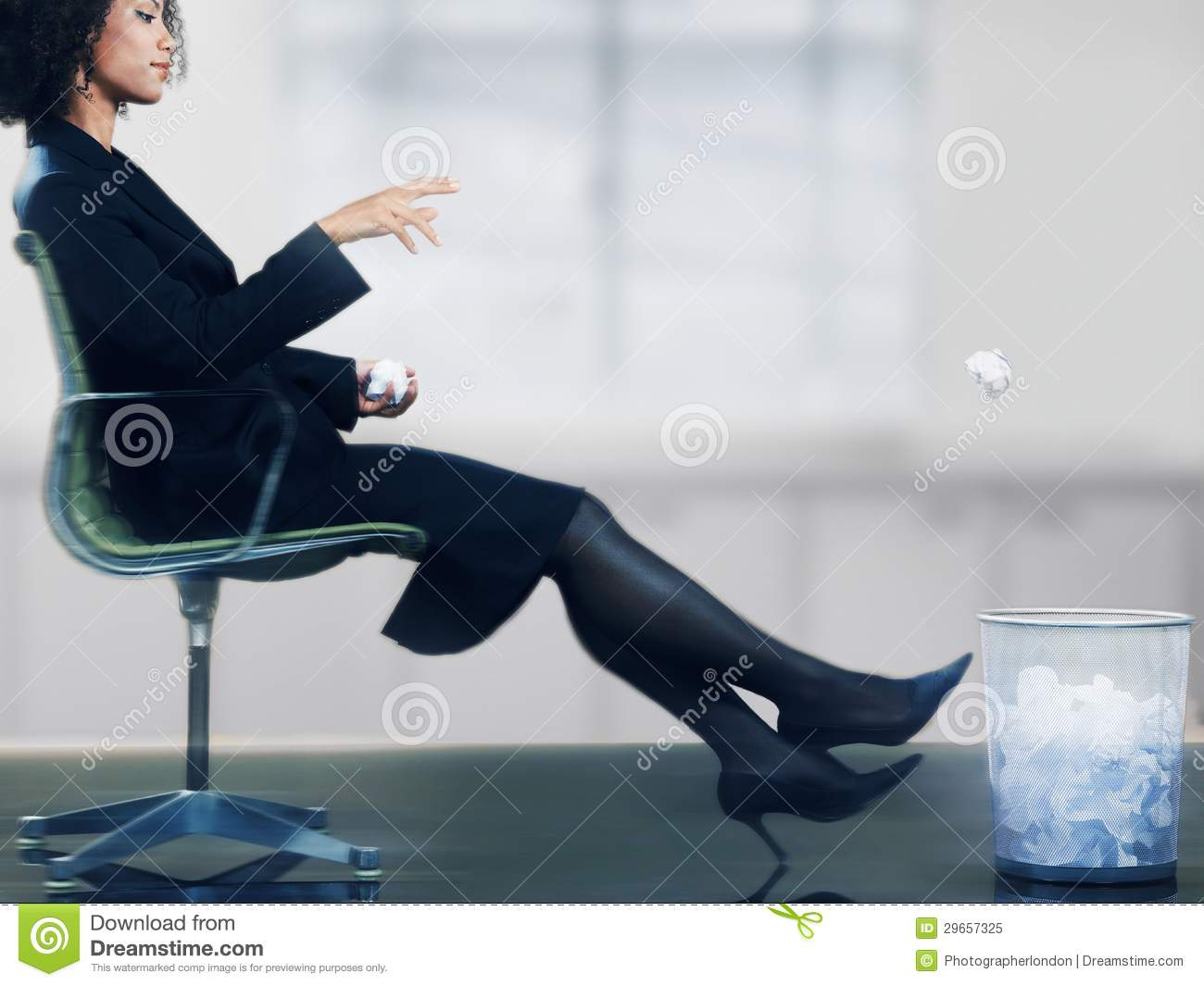 Businesswoman Throwing Paper Ball Into Dustbin Stock Image