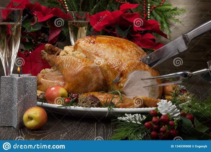 Carving garnished roasted Christmas turkey with grab apples, sweet  chestnut, cranberry, Christmas ornaments, candles, and pine cones