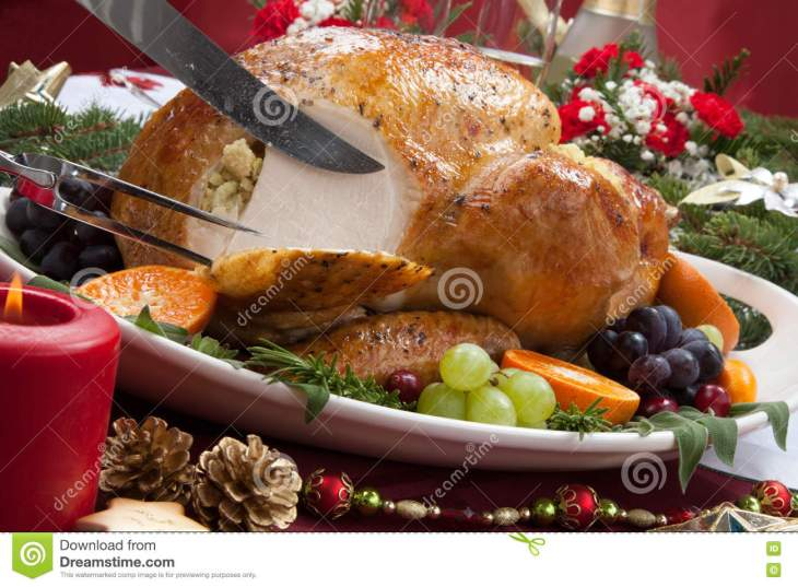 Carving roasted herb rubbed turkey garnished with fresh grapes, oranges,  and cranberry is ready for Christmas dinner. Ornaments, Champagne, candles  ...