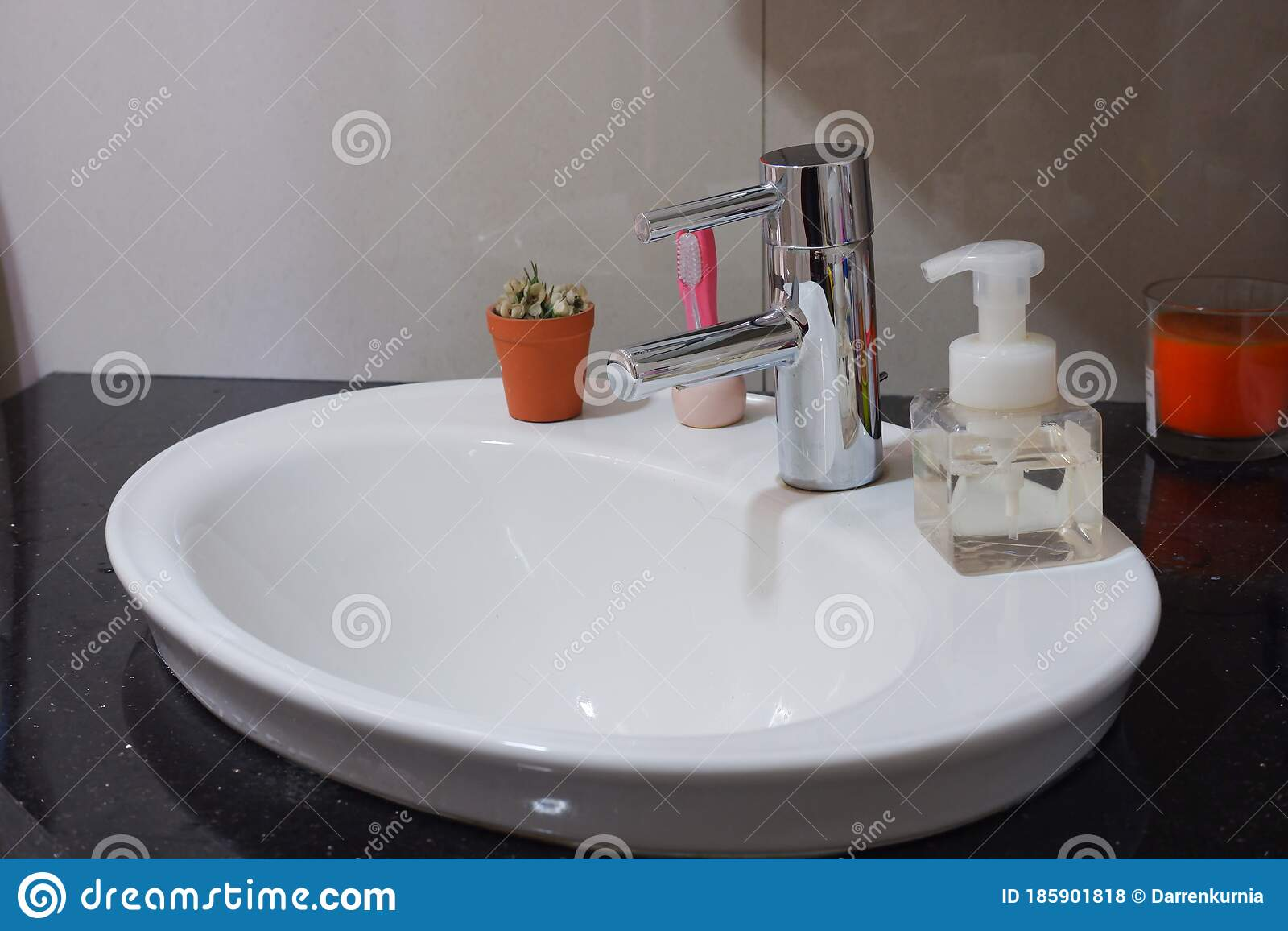 a ceramic sink with flowers toothbrush and a hand foam bottle beside it beautiful and minimalist bathroom stock photo image of kelapa famp 185901818