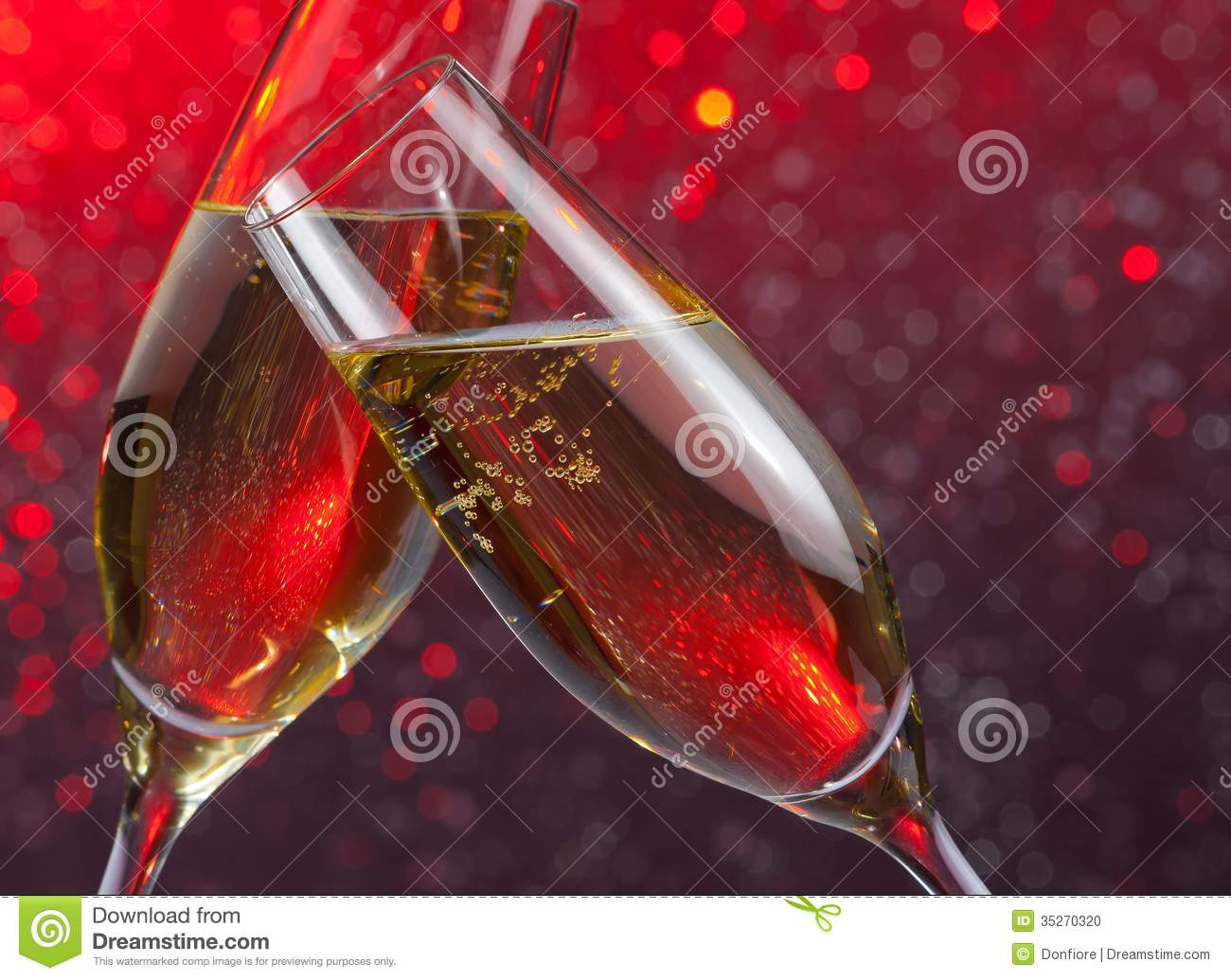 Champagne Flutes With Gold Bubbles On Red Light Bokeh