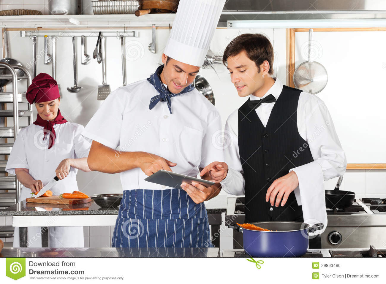 Waiter And Chef Using Digital Tablet In Kitchen Stock